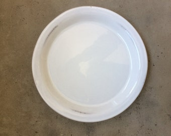 White plate from Crate & Barrel, USA. Irregular glazing at the edge, thick round edge, 21 cm diameter