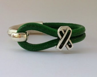 Dwarfism Awareness leather bracelet with a silver half cuff and an open silver awareness ribbon.