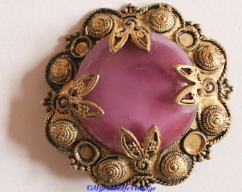 Pink circular stone vintage brooch with gold colour ornate surround.