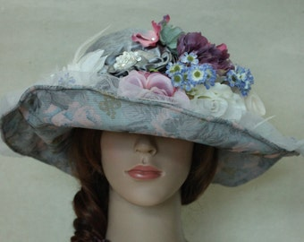 A Silver Gray Fabric Church Hat With Mesh And Flowers