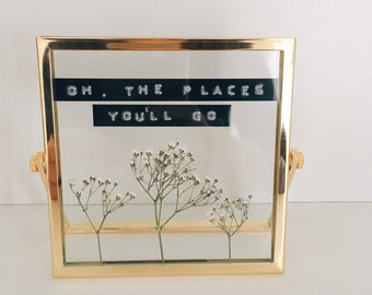 Gold glass frame with pressed flowers and  'the places you'll go' quote