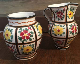 Set of vase and pitcher has decoration of flowers. Italy