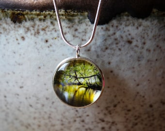 A hand crafted silver plated 20mm or 16mm pendant featuring an original photograph taken in the Cairngorms, Scotland