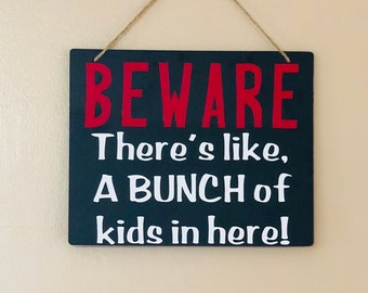 Beware There's like a bunch of kids in here sign, funny daycare sogn, funny classroom sign, funny family door sign.
