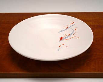 Shallow white porcelain bowl with red and black detail