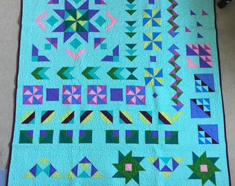 """Finished geometric quilt in solid colors on a teal background - 58"""" x 71"""""""
