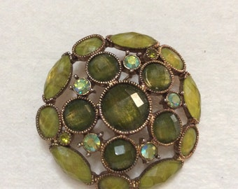 Faceted green rhinestone circle brooch pin.