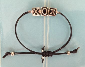XO hugs and kisses bracelet on black leather cord
