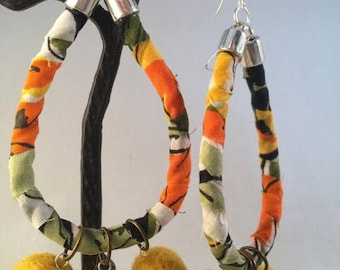 Handcrafted and hand assembled boho style earrings featuring felted pom poms and jungle print fabric