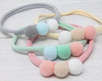 Three pom pom sweet baby headband handmade in the UK nylon skinny elastic newborn photography prop