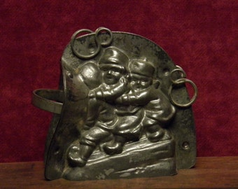 Antique Christmas three part chocolate mold of three children riding on a sled by Anton Reiche