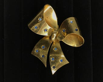 vintage gold tone bow pin with light blue gemstones