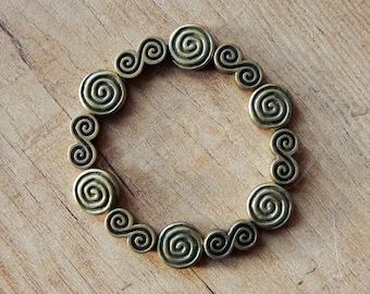 "Swirls beaded elastic bracelet ""Madre"" in bronze tone"