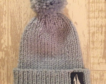 Hatties Attic hand knitted light blue bobble hat with the Hatties Attic logo