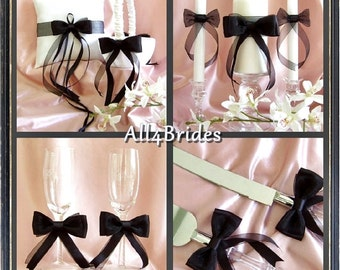 Black and white wedding ring pillow, basket, cake serving set, toasting glasses and unity ceremony candles.