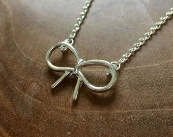 Bow - necklace with a cute little bow pendant. silvertone, trend, hipster, modern, minimal, outline, fashion