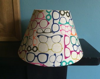 30cm coolio/square/drum/round table/ceiling lampshade. Beige background with multicoloured glasses.