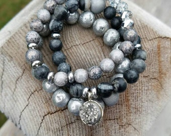 Black and grey beaded bracelet and a rock charm.