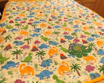 Baby Blanket with different colored dinosaurs and appliqued cute green dinosaur.