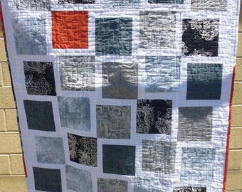 Gray and white crib or lap quilt, with a splash of orange