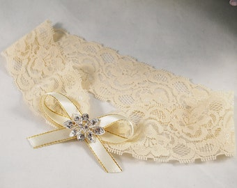 Cream lace stretch garter on the bride's leg with a beautiful brooch and satin bow