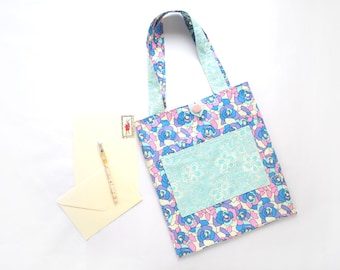 Reversible cotton tote bag/book bag with pockets with roses in blue, purple, pink and off-white; and white flowers on light turquoise