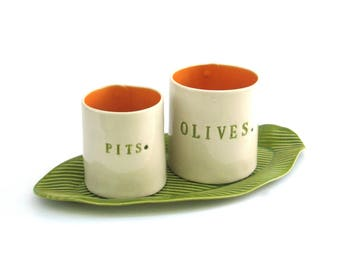 olives and pits  ....  hand built porcelain containers on a tray  ...  vessels and tray