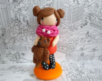 Girl holding a snood with pink polymer clay