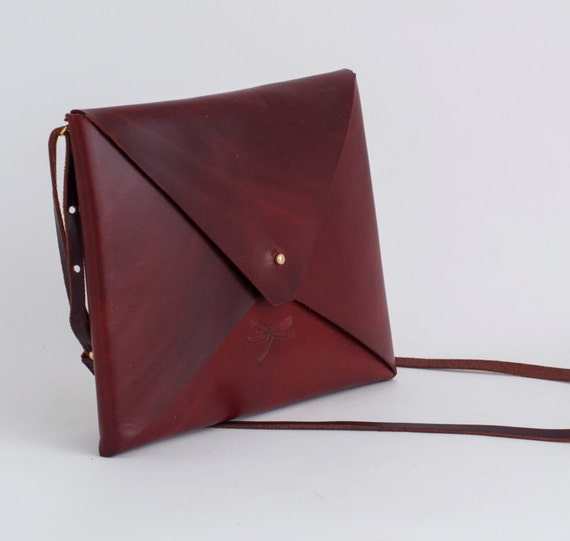 Unisex Leather bag, with rembable strap and gold button. Simple and minimalist.