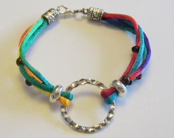 Original bracelet with multicolored cords fastened around a large silver hammered look ring