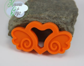 "Teething ring. Orange ""carriage heart"" shape."