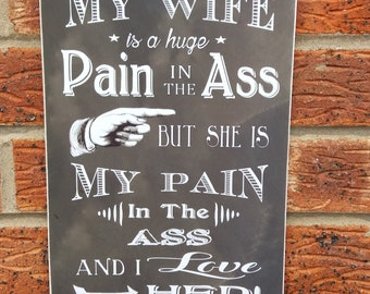My wife is a hugh pain in the ass but I love her sign wooden plaque