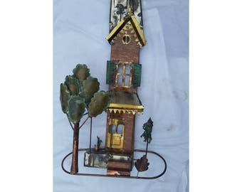 Metal sculpture cat on tin roof house