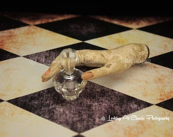 mannequin hand, creepy art photo, eerily elegant hand with crystal perfume bottle, mysterious and macabre, harlequin check