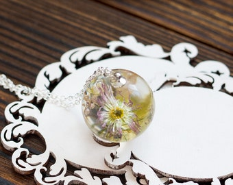 Pendant with a bouquet of daisies and wild herbs.