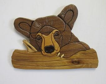 Intarsia bear cub on branch