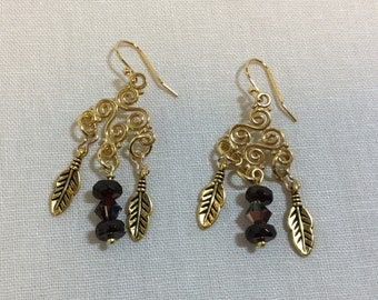 Gold chandelier earrings with garnet rondels and feathers