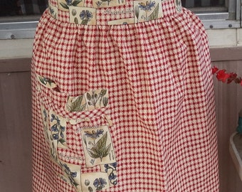 1/2  apron  in an old fashioned print fabric has a checked skirt and a contrast waistband and pocket.