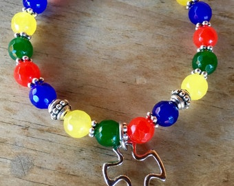 Jade gemstone beads in autism awareness colors with puzzle piece charm - stretch yoga bracelet
