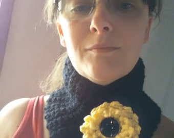 Black neckwarmer with yellow flower and black button