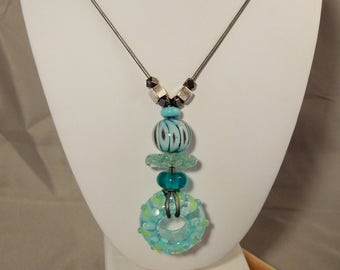 Artisan glass bead necklace with pale aqua, blue, and teal glass beads on metallic silver leather cord