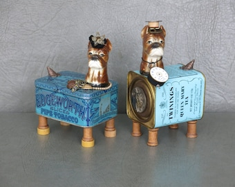 Pair of steampunk dog sculptures.  Porcelain boxer heads affixed to vintage tins, spool feet, watch parts, gears, jewelry, found objects.