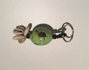 Keychain made of ceramic and cowrie shells