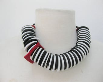 All rubber cut circles on a short necklace-black and white with a red square-short necklace-very light weight.