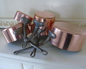 French. Set of five 1mm,  copper pans with cast iron handles.  Tin lined.  In excellent  condition.   Fabrication Francais.