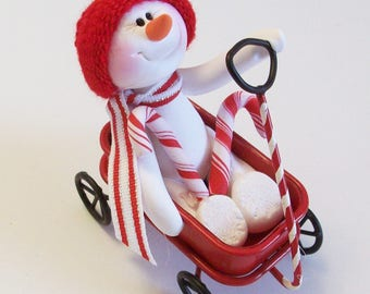 Snowman riding a peppermint wagon with candy canes: snowman decoration table top