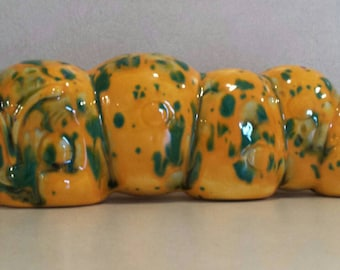Ceramic caterpillar. Orange with green and white specks. Angry or scowl look.