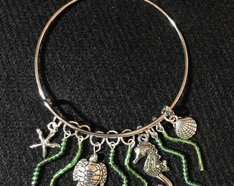 a turtle, shells and seahorse with seaweeds on a sliver bange bracelet