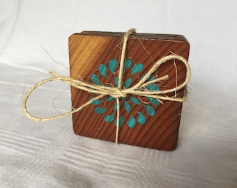 Reclaimed wood coasters with teal stenciled flower design