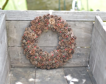 Door wreath with pine cones and red berries - season autumn/winter.